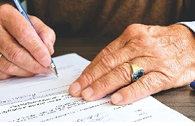 Picture of man's hands signing document.